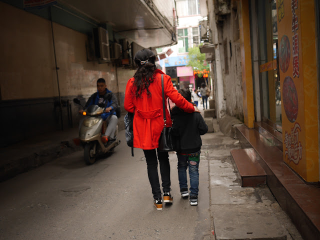 woman wearing a red jacked with arm around a boy as they walk down Wuya Lane in Shaoguan, Guangdong