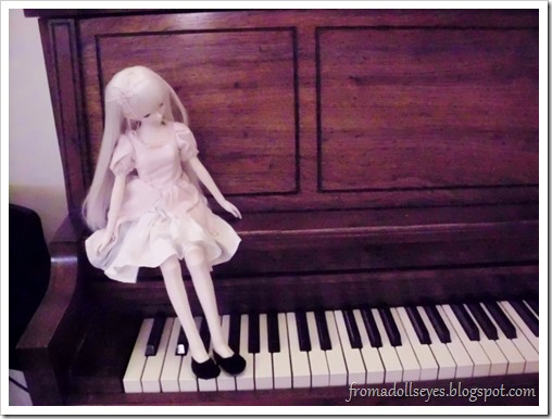 A ball jointed doll sitting on a piano.
