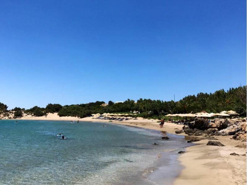En lang sandstrand som kurver seg rundt det turkise vannet i bukten. Trær i bakgrunnen, noen store steiner på høyre side.
