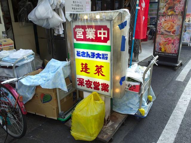 店頭に置かれた立看板。脇には野菜などの入ったダンボールが積み重なってる。