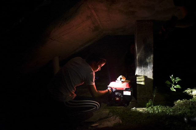 Karina Santiago Gonzalez works on a small electricity generator in Morovis, Puerto Rico, in December 2017. Photo: Carlos Giusti / AP