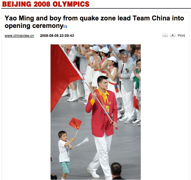 photo of boy with upside-down Chinese flag walking with Yao Ming during the opening ceremony for the 2008 Summer Olympics in Beijing