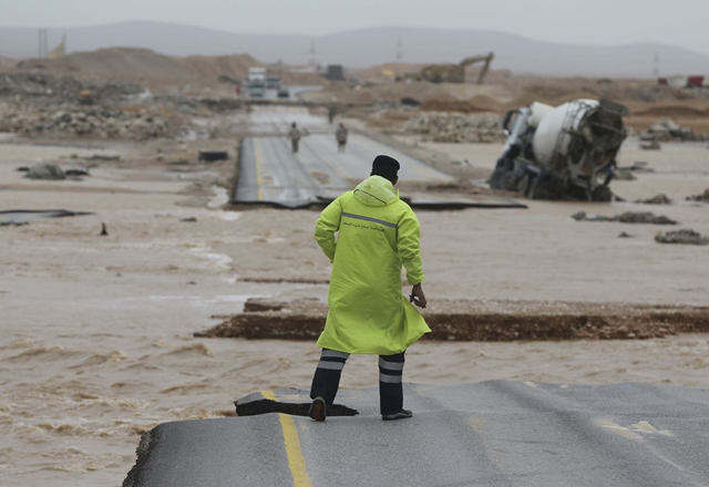 An Omani civil defence staff visits a road which has been cut by the flood water after Cyclone Merkunu in Salalah, Oman, Saturday, 26 May 2018. Cyclone Merkunu blew into the Arabian Peninsula on Saturday, drenching arid Oman and Yemen with rain, cutting off power lines and leaving at least one person dead and 40 missing, officials said. Photo: Kamran Jebreili / Associated Press