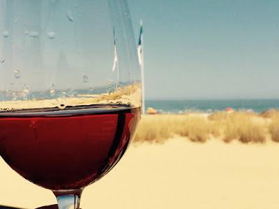 Utsikt mot stranden og et glass rosevin.