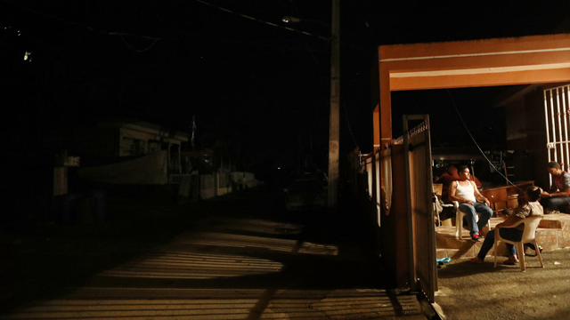 People sit at a home lit by a generator, as surrounding homes remain dark, more than two weeks after Hurricane Maria hit the island, on 7 October 2017 in San Isidro, Puerto Rico. Photo: Mario Tama / Getty Images