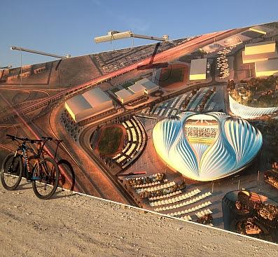 Illustrierter Bauzaun Fußball-Stadion-Bau in Al Wakrah für die Fifa-WM 2022 mit dem Entwurf der irakisch-englischen Architektin Zaha Hadid; MTB Specialized Crave MTB Hardtail 29''