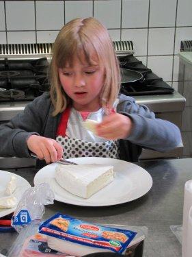 Jozefien is goed bezig met plakjes Brie te snijden. Niet gemakkelijk want dat is van die kleverige kaas.