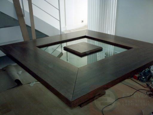 mesa de comedor de pie central cuadrado sobre de vidrio y extensiones en madera