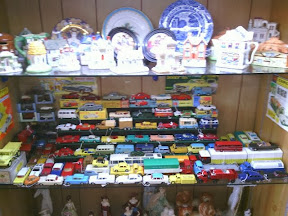 A colourful shelf of old corgi & dinky toy cars in amongst antiques