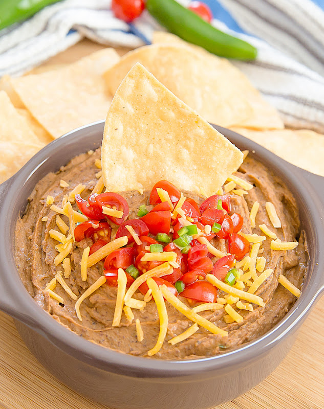 photo of a bowl of Southwest Black Bean Hummus Dip garnished with cheese, tomatoes, and tortilla chip