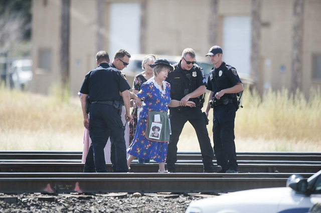 Nancy Nelson, a member of the activist group 'Raging Grannies', is escorted to a police cruiser after she and two other protesters blocked railroad tracks near 2302 East Trent to protest the movement of oil and coal trains through Spokane on Wednesday, 31 August 2016, in east Spokane, Wash. Photo: Tyler Tjomsland / The Spokesman-Review