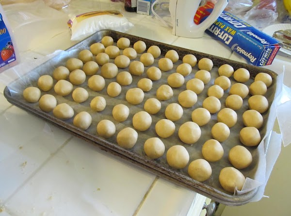 Pinch off little pieces of the dough and roll into balls. Place rolled balls...