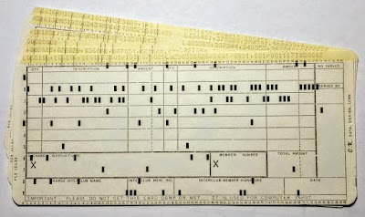 80-column punch cards. Each column of the card holds a character, represented by the holes punched in the column. THE text at the top of the card shows what is in each column. Black paper behind the first card makes the holes more visible.