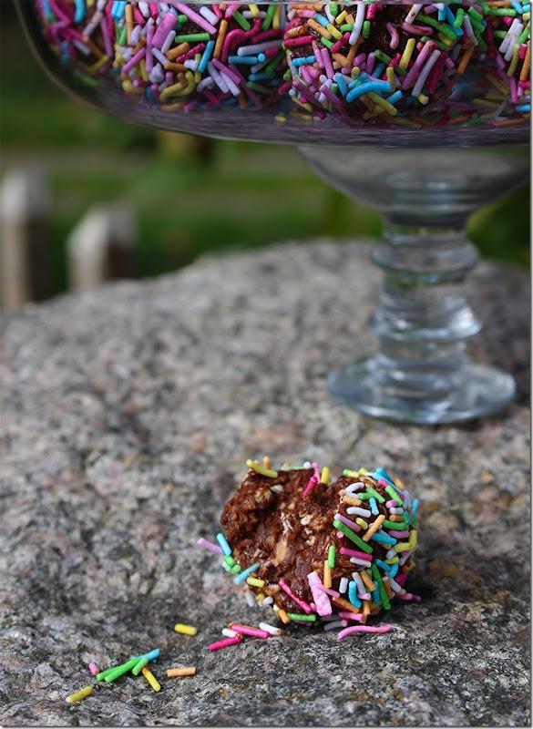 Närbild på tuggad chokladboll med färgglatt strössel runt om.