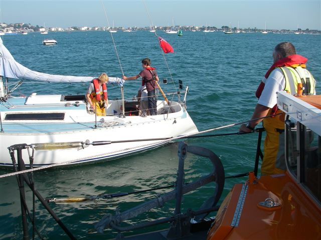 30 September 2011 - Coxswain Jonathan Clark looks on from the ALB as crew member Ed Davies inspects the yacht and chats to the family onboard