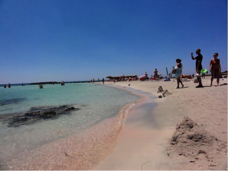 Små bølger som slår mot stranden. Rosa sand kan skimtes under bølgene.
