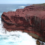 Red cliffs with waves crshing (105286)