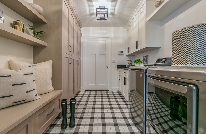 A laundry room with cabinets and shelves
