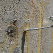 Attachment of the grease gun filled with polyurethane concrete foundation crack repair material