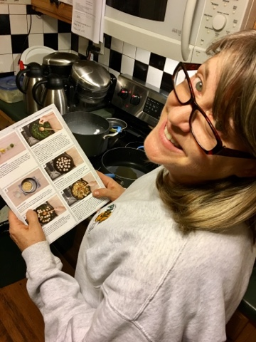 Woman in grey sweatshirt wearing glasses reading Blue Apron recipe while cooking in kitchen with black and white tiles