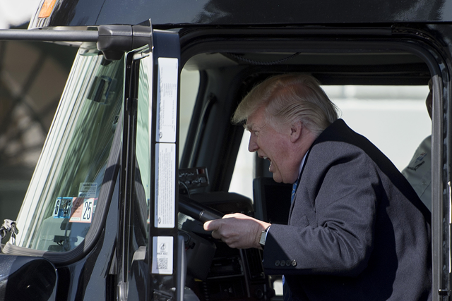 President Donald Trump climbed into the cab of a Mack truck parked on the lawn Thursday, 23 March 2017, to welcome trucking industry representatives to the White House. Photo: TIME