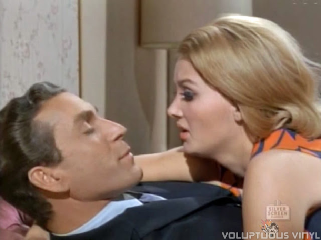 Barbara Bouchet and Adam Chance lay around.