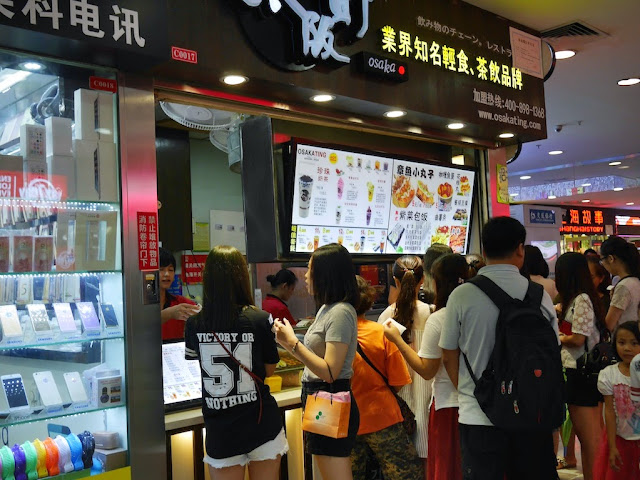 "young woman wearing a ""Victory or Nothing"" shirt at a Japanese take-out restaurant in Zhuhai"