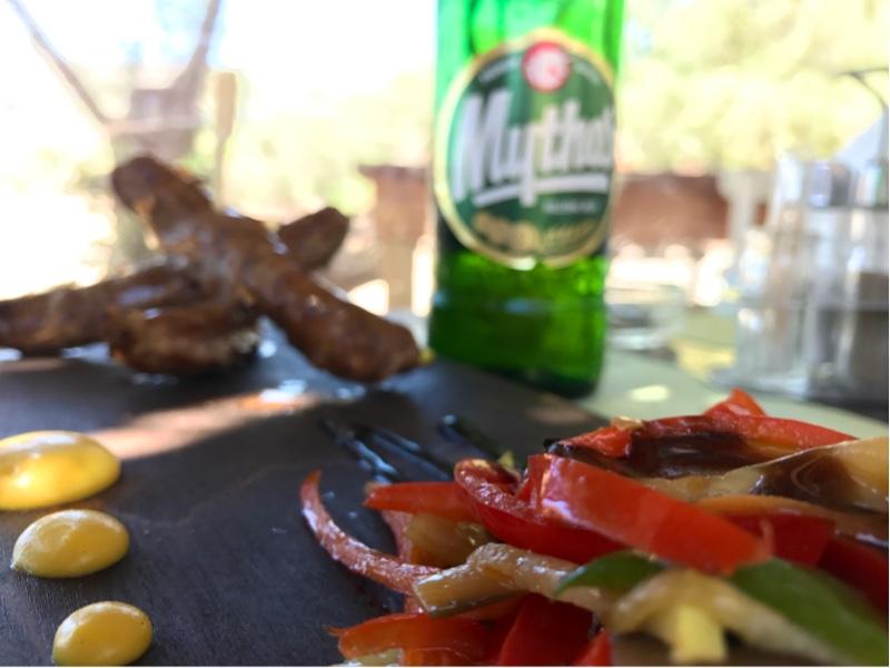 3 tynne pølser i stabel ved siden av en flaske Mythos øl i bakgrunnen. I forgrunnen en liten haug med grønnsaker.