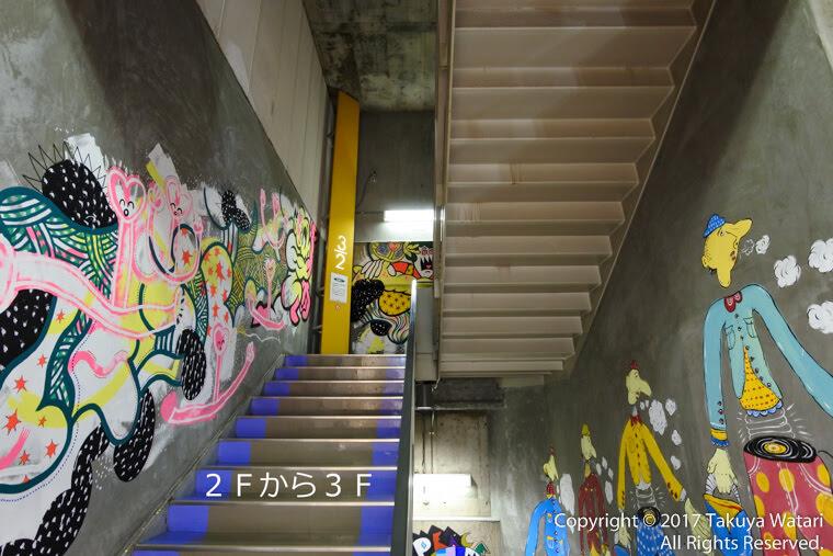 梅田ロフトの階段に2Fから3Fと入力した写真。グラフィティアートがたくさん見える