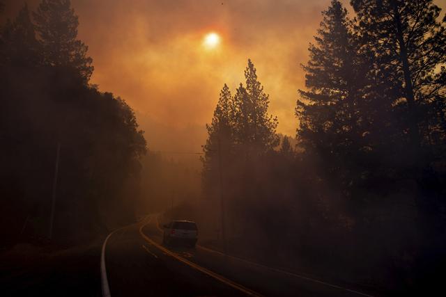 A vehicle drives through smoke near Pulga, Calif., Sunday, 11 November 2018. Photo: Noah Berger / AP Photo
