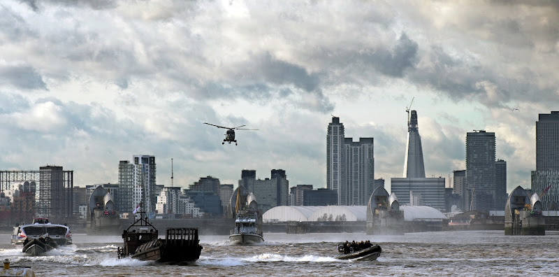 Photo: The Metropolitan Police and Royal Marines in offshore landing craft, rigid inflatable boats (RIBs), a Lynx helicopter and other craft speed along the river Thames near Woolwich during a safety and security planning exercise for the London 2012 Olympic Games in London on January 19, 2012. The Royal Marines joined 44 police officers in a police-led safety and security exercise in preparation for the Games in London.  AFP PHOTO / ADRIAN DENNIS (Photo credit should read ADRIAN DENNIS/AFP/Getty Images)