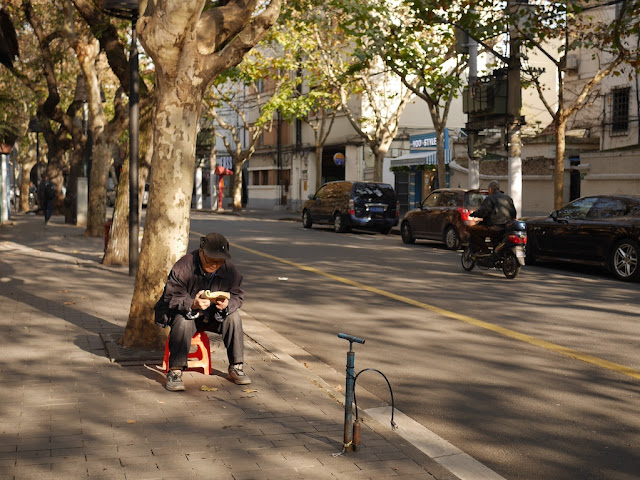 man sitting next to road reading a book with a bicycle tire pump nearby