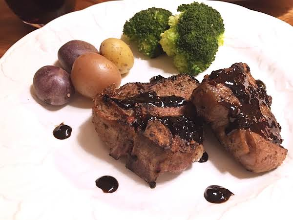 Two Lamb Chops With Dark Sauce Drizzled On Top On A White Plate With Baby Potatoes And Broccoli.