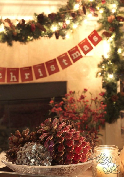 Glittered pinecones in front of christmas mantel