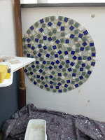 Stones of glas and marble being fixed, little real siver- tiles in between