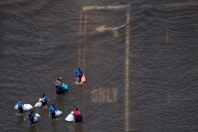 Aerial view of a group of people carrying supplies through Hurricane Harvey floodwaters in Port Arthur, Texas. Photo: Adrees Latif / REUTERS
