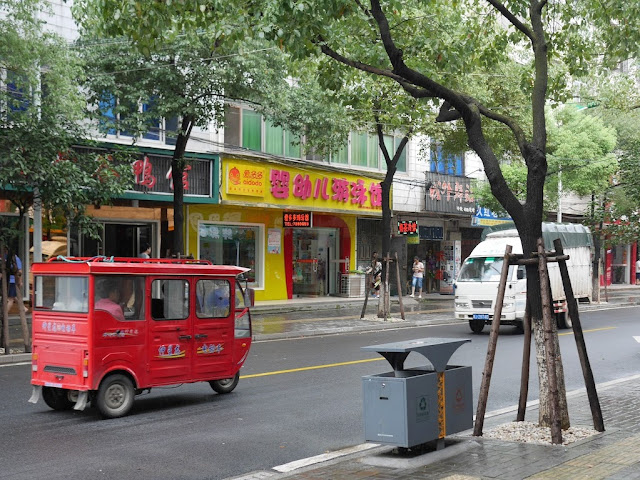 a red auto-rickshaw on a street