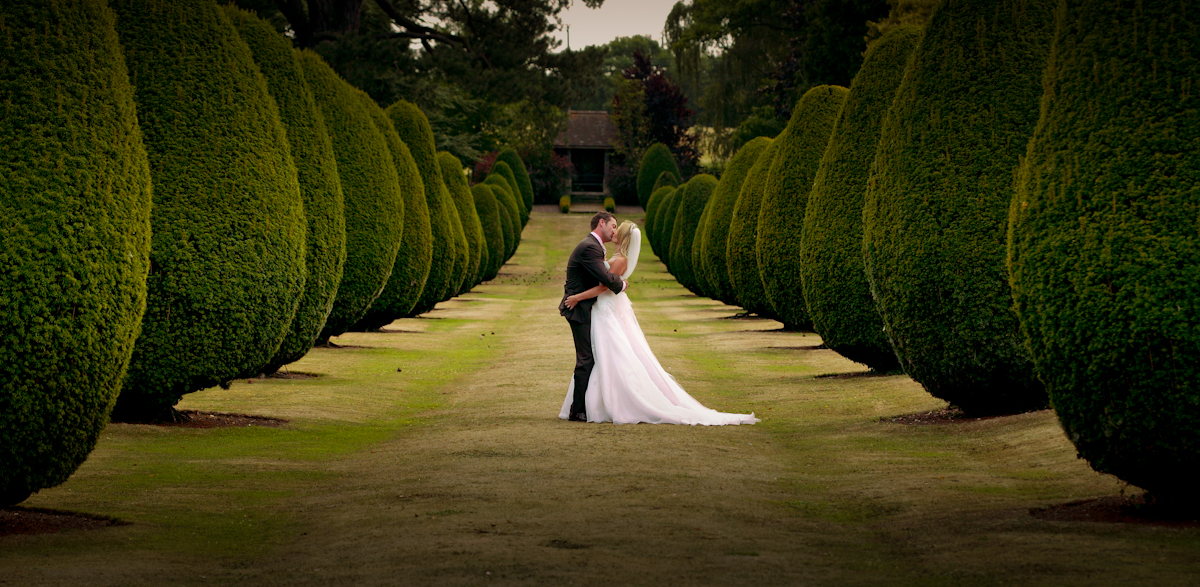 Bride and groom embrace on tree lined avenue