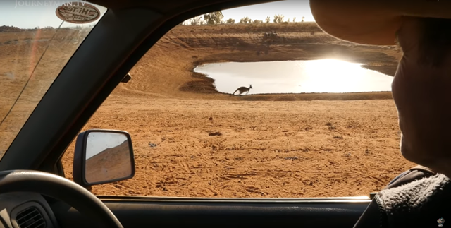 Screenshot from the short film, 'Australia's Drought', shows a kangaroo jumping in front of a depleted reservoir. 'Australia's Drought' documents how the extreme drought is affecting farmers in the Australian outback in 2018. Photo: Journeyman Pictures