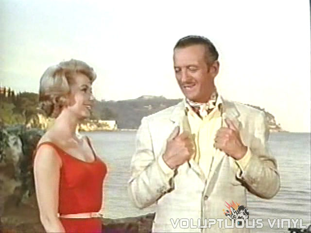 Shirley Jones in a red dress and David Niven in a white suit.
