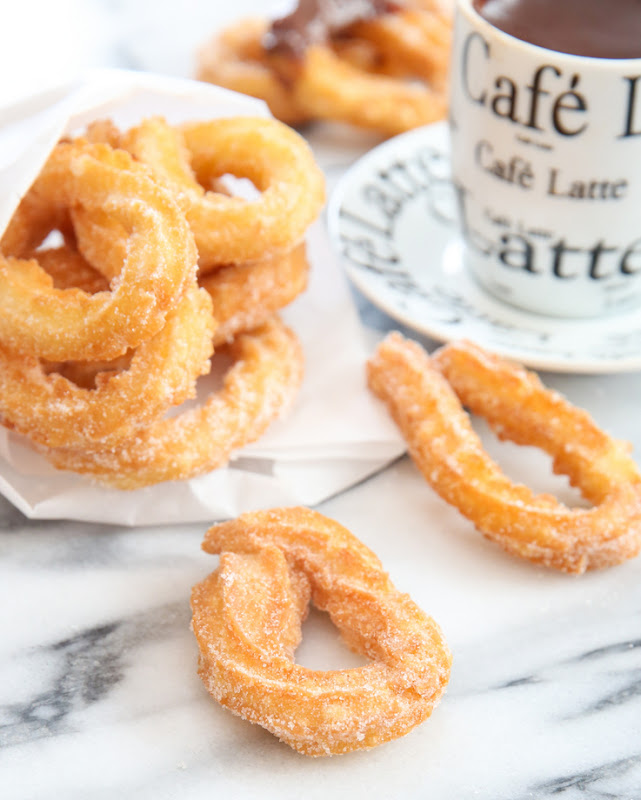 photo of two churros with a pile of churros in the background