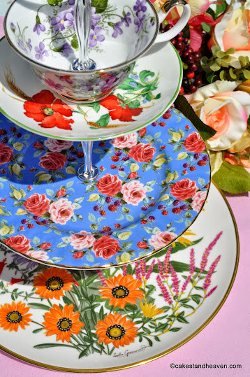 colourful ecletic three-tiered cake stand with teacup top