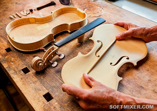 Elderly person building a violin