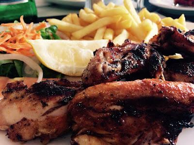 Stekt kylling med pommes frites og salat i bakgrunnen.