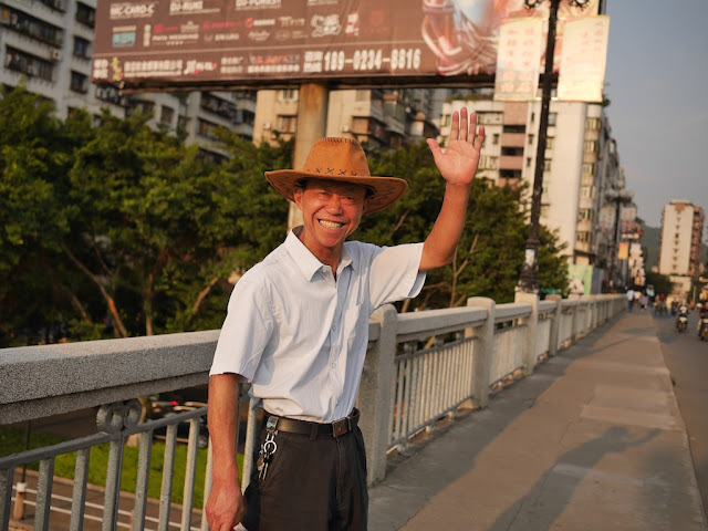 smiling man in Shaoguan wearing a hat and waving to the camera