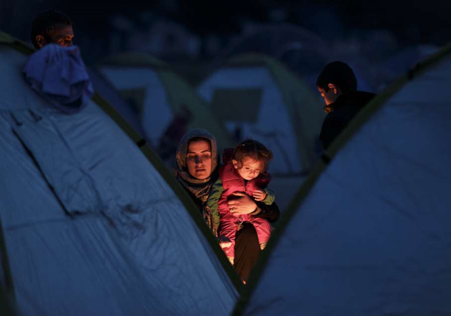 A woman holds a baby sitting by a fire near the northern Greek border station of Idomeni, Thursday, 3 March 2016. Some thousands of refugees and migrants wait on the border between Greece and Macedonia and about 30,000 refugees and other migrants are stranded in Greece. Photo: Vadim Ghirda / AP Photo