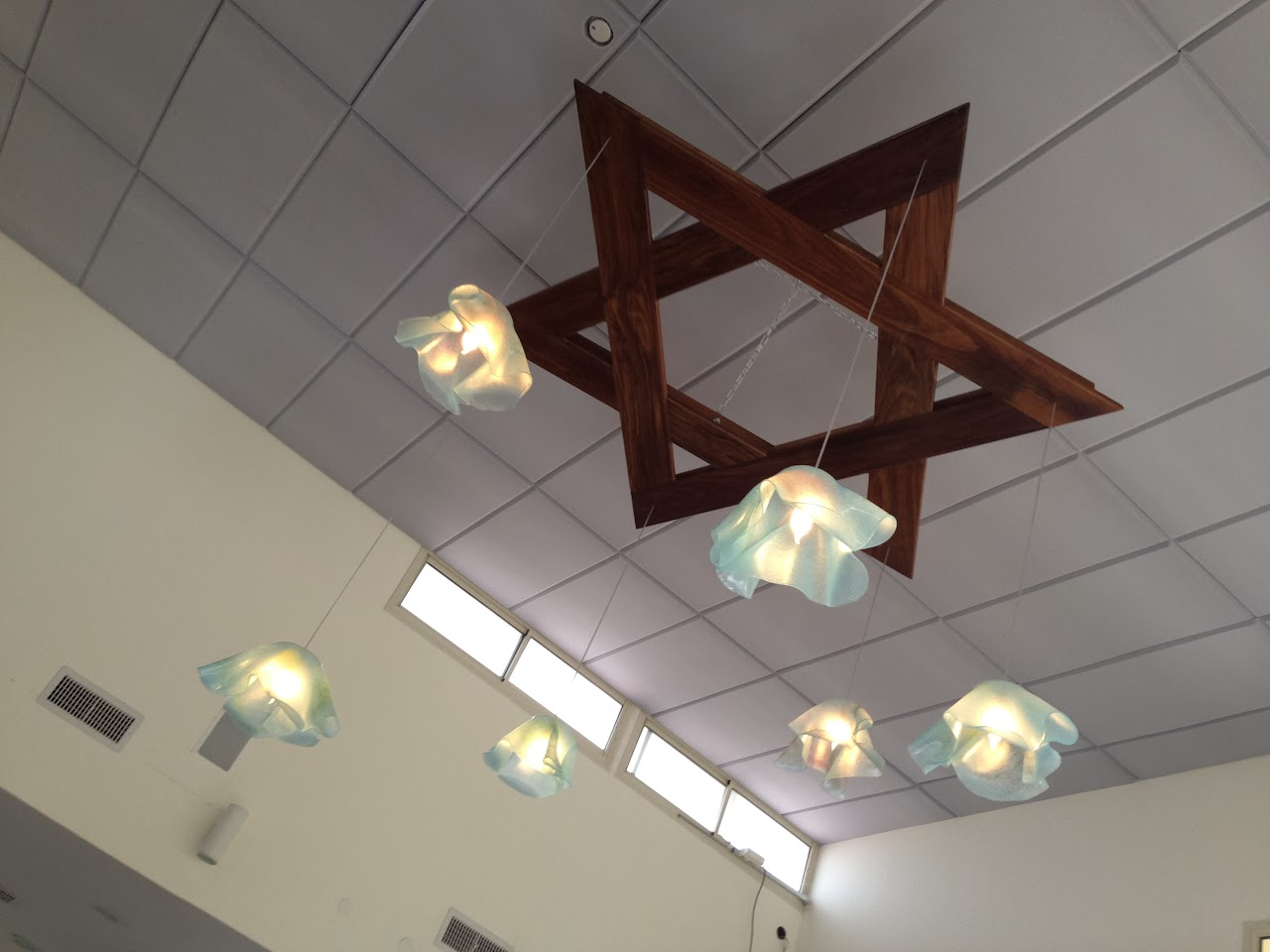 נברשת מעוצבת בצורת מגן דוד עם 6 מנורות מזכוכית חלבית בגוון תכלת. A chandelier in the shape of Magen David with 6 light-blue matte glass lamps.
