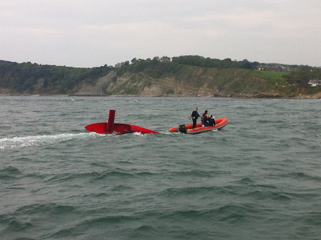 20 May 2012: Capsized dinghy being towed by sailing club safety boat in Swanage Bay after struggling with the tide and wind on Peveril Ledge. Photo: RNLI/Poole Dave Riley