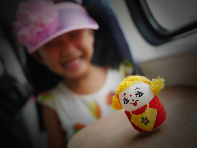 girl in pink hat smiling at an egg doll made out of two ping pong balls