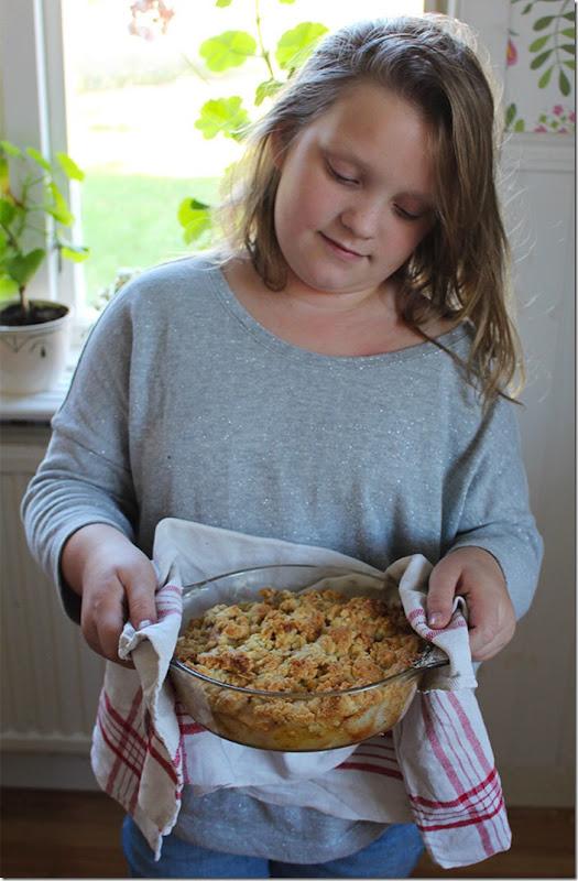 </p>Min dotter Linnea håller i en nybakad paj med en röd-vit-rutig kökshanduk.
